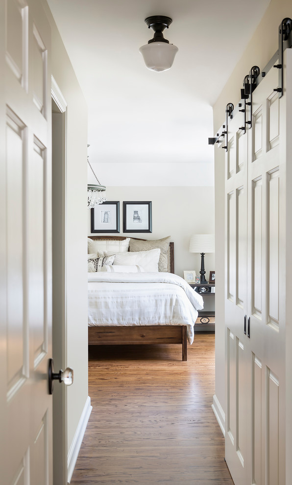 Inspiration for a mid-sized timeless master medium tone wood floor bedroom remodel in Minneapolis with no fireplace and beige walls