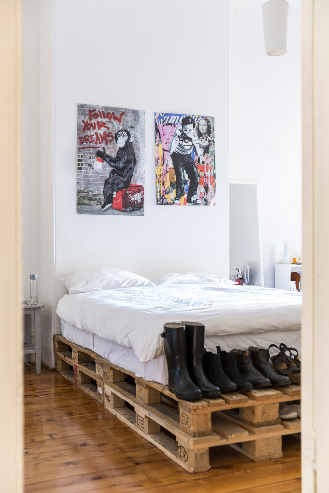 Example of an eclectic medium tone wood floor bedroom design in Sydney with white walls