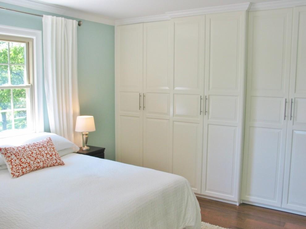 Elegant master medium tone wood floor bedroom photo in Cincinnati with blue walls