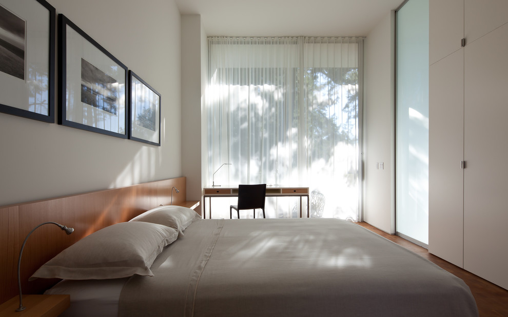 Inspiration for a modern medium tone wood floor bedroom remodel in Seattle with white walls