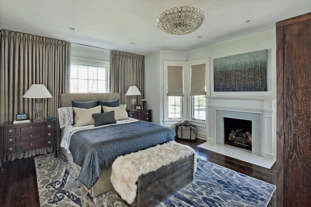Example of a classic dark wood floor bedroom design in Chicago with gray walls and a standard fireplace