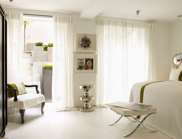 This is an example of a contemporary bedroom in London with white walls, painted wood flooring, no fireplace and white floors.