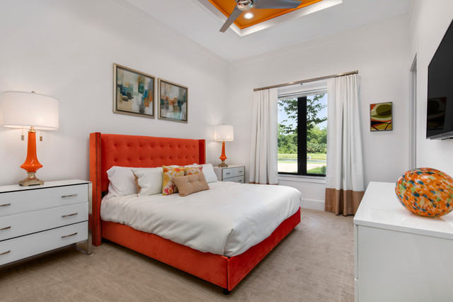 Inspiration for a large modern guest carpeted bedroom remodel in Orlando with orange walls and no fireplace