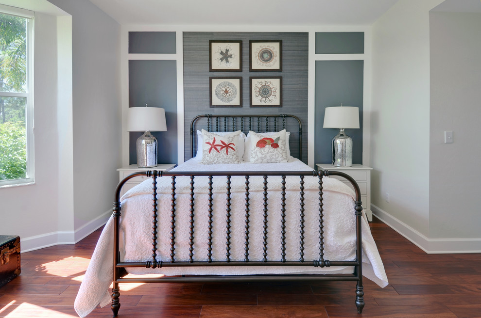 Inspiration for a beach style guest medium tone wood floor bedroom remodel in Miami with white walls