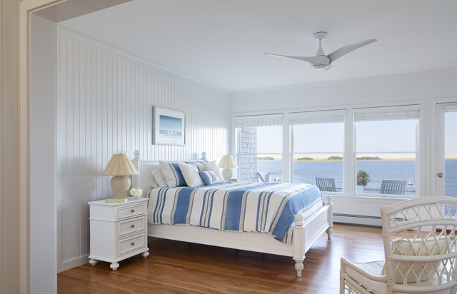 Example of a coastal medium tone wood floor and brown floor bedroom design in Boston with white walls
