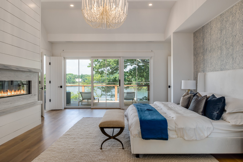 Bedroom - transitional master medium tone wood floor and brown floor bedroom idea in New York with white walls, a ribbon fireplace and a stone fireplace