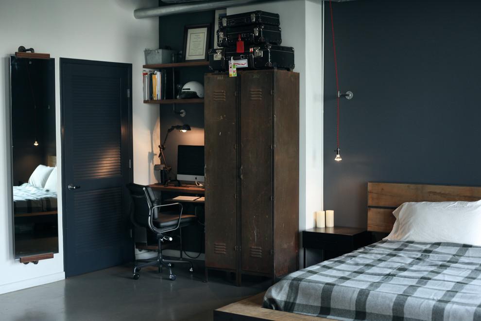 Immagine di una camera da letto industriale con pareti blu, pavimento in cemento e nessun camino