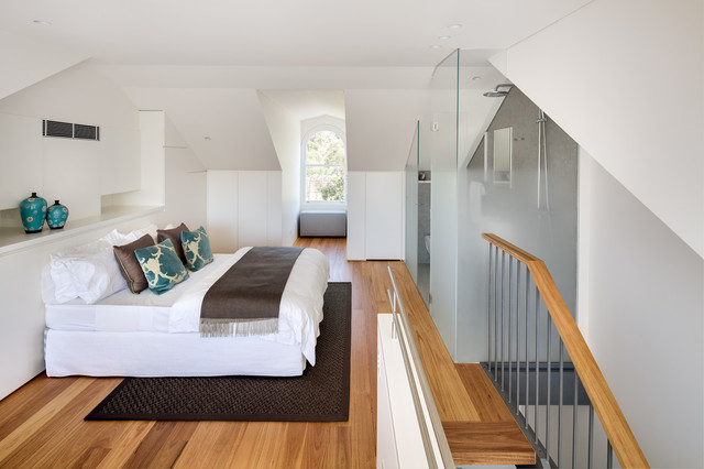 Mid-sized trendy loft-style medium tone wood floor bedroom photo in Sydney with white walls and no fireplace