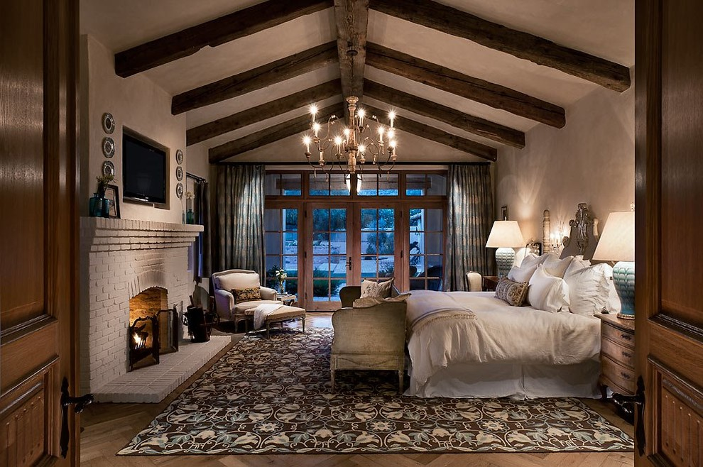 Example of a southwest master dark wood floor bedroom design in Phoenix with beige walls and a standard fireplace