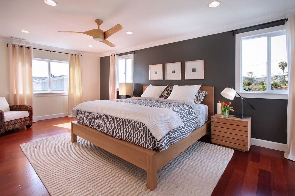 Example of a transitional medium tone wood floor bedroom design in Orange County with black walls and no fireplace