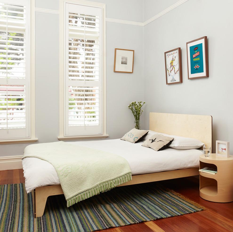 Trendy medium tone wood floor bedroom photo in Melbourne with gray walls