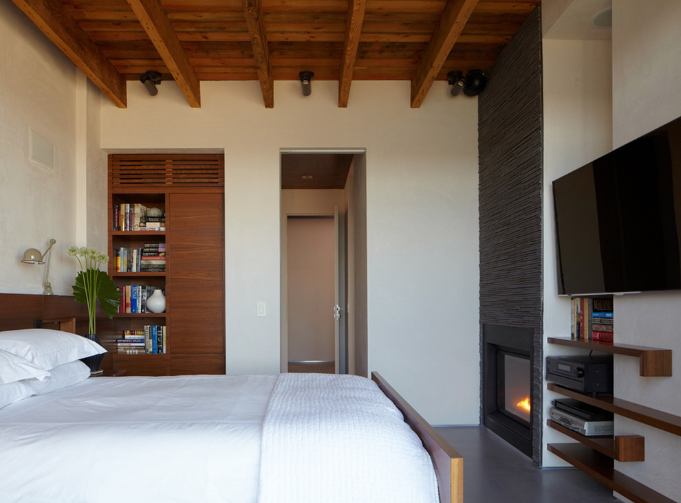 Example of a mid-sized minimalist concrete floor bedroom design in New York with white walls, a standard fireplace and a metal fireplace