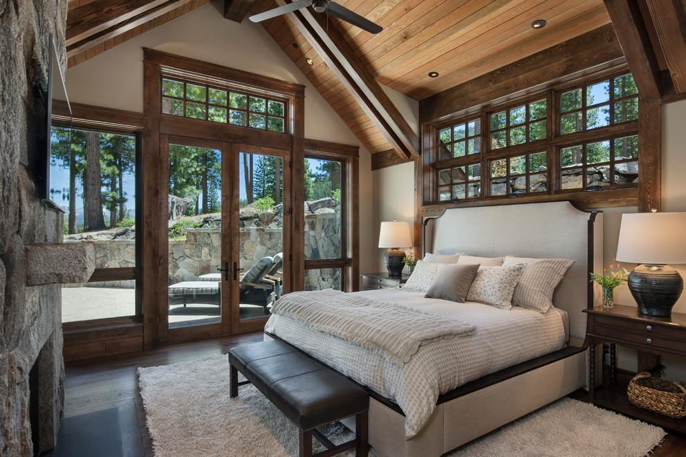 Esempio di una grande camera matrimoniale stile rurale con pareti bianche, parquet scuro, camino classico, cornice del camino in pietra, pavimento marrone e letto davanti alla finestra
