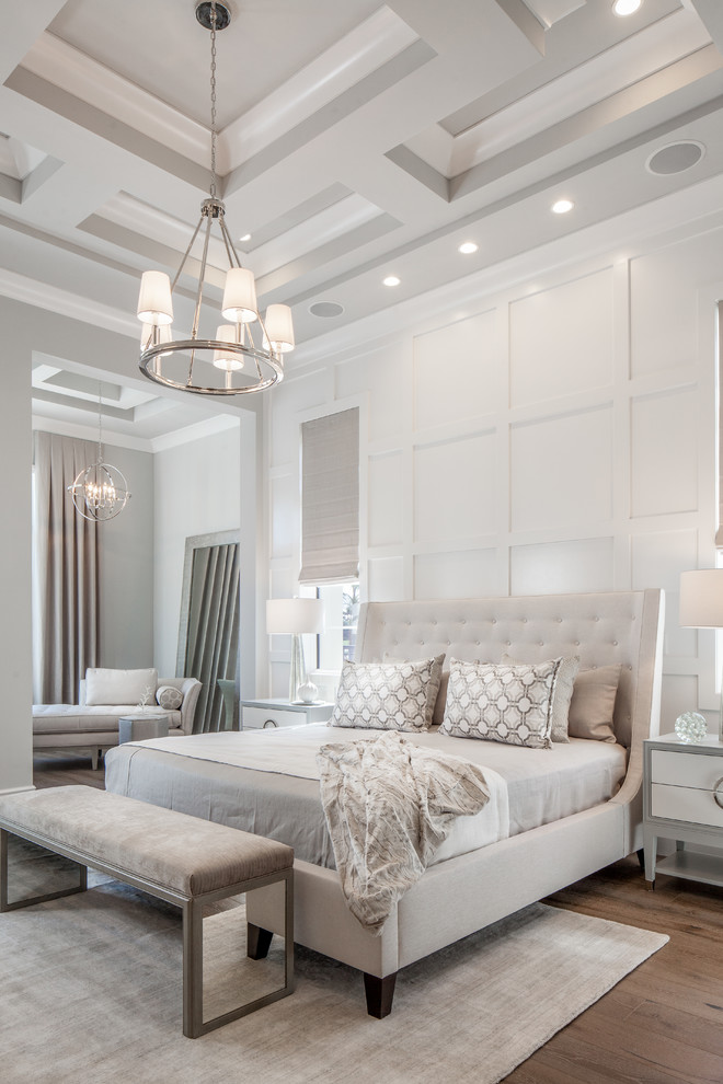 Example of a transitional medium tone wood floor and brown floor bedroom design in Miami with white walls