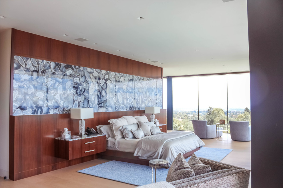 Inspiration for a large modern master light wood floor and white floor bedroom remodel in Los Angeles with beige walls, a ribbon fireplace and a stone fireplace