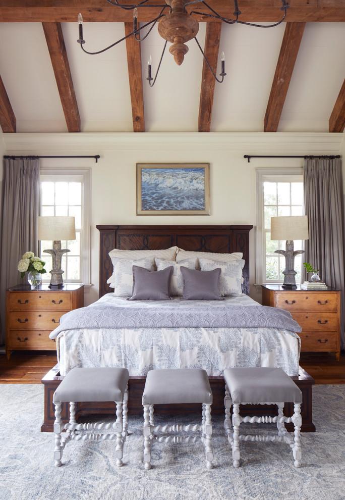 Beach style medium tone wood floor and brown floor bedroom photo in Other with white walls