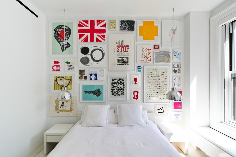 Example of a small danish light wood floor bedroom design in New York with white walls
