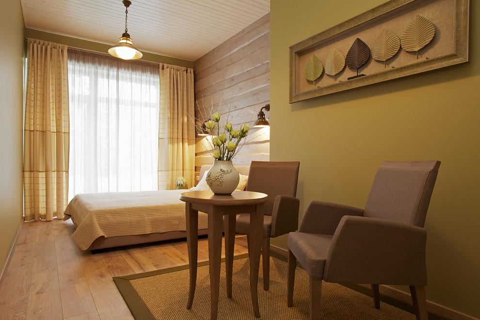 Trendy medium tone wood floor bedroom photo with green walls