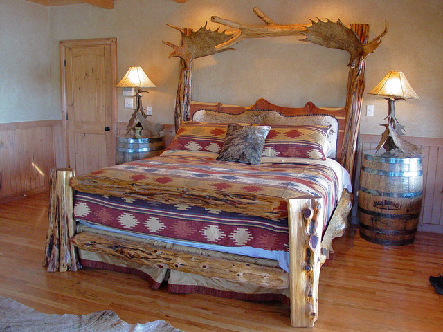 Rustic log bed with brindle cowhide headboard and moose for Raw wood bed frame
