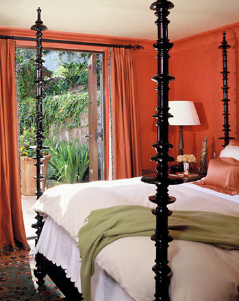 Orange walls emphasize the extreme height and turned shapes of dramatic bed