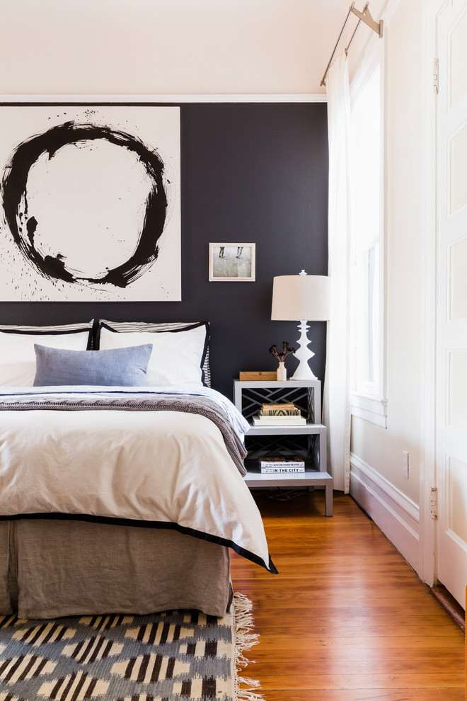 Inspiration for a transitional master medium tone wood floor bedroom remodel in San Francisco with black walls