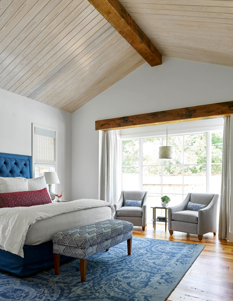 Inspiration for a farmhouse master medium tone wood floor bedroom remodel in Dallas with white walls