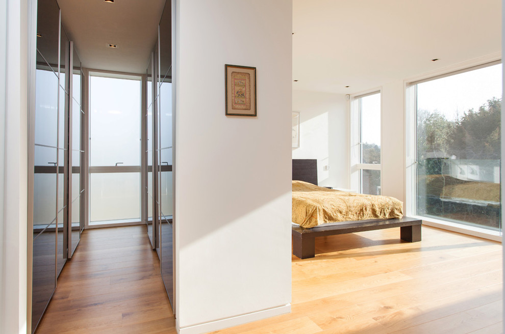 Inspiration for a contemporary light wood floor bedroom remodel in Hampshire with white walls and no fireplace