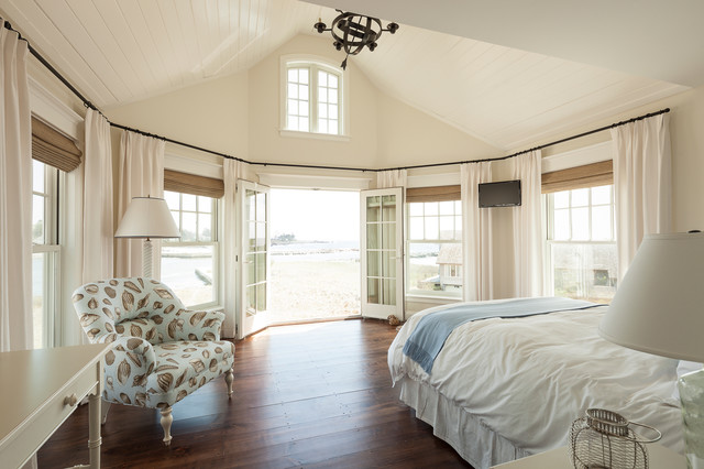 Inspiration for a beach style dark wood floor and brown floor bedroom remodel in Portland Maine with beige walls