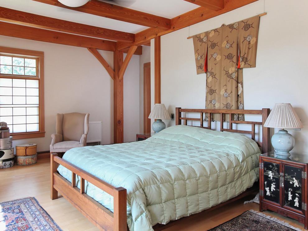 Zen light wood floor bedroom photo in Portland Maine with white walls