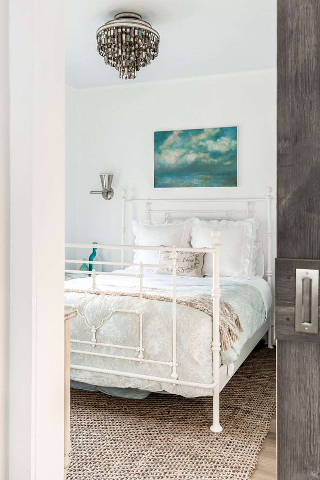 Example of a mid-sized beach style master medium tone wood floor bedroom design in New York with white walls
