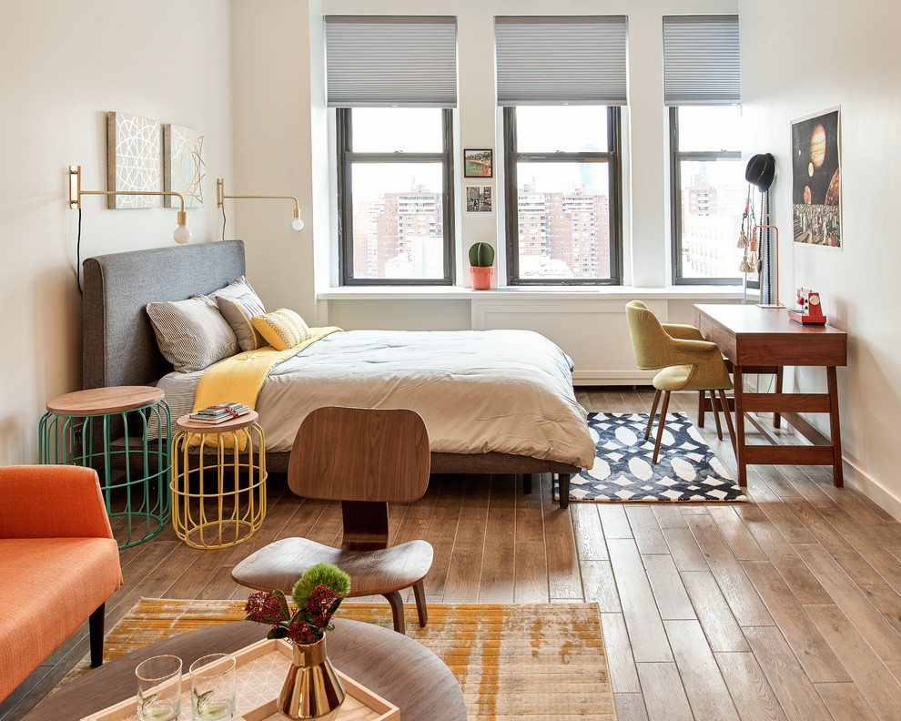 Inspiration for a small 1960s loft-style light wood floor and brown floor bedroom remodel in New York with white walls