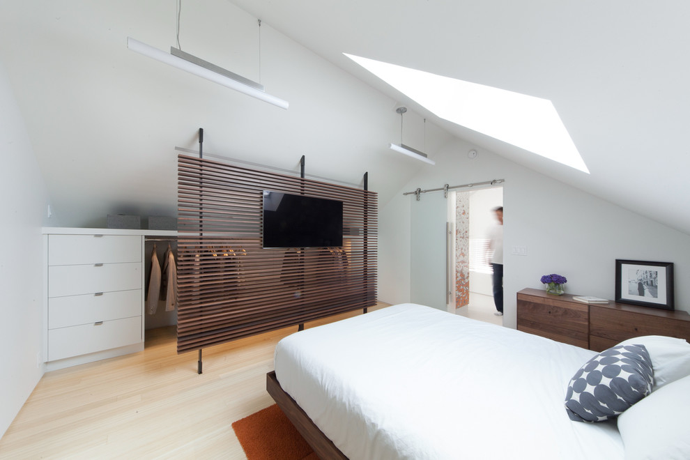 Example of a trendy light wood floor bedroom design in Seattle with white walls