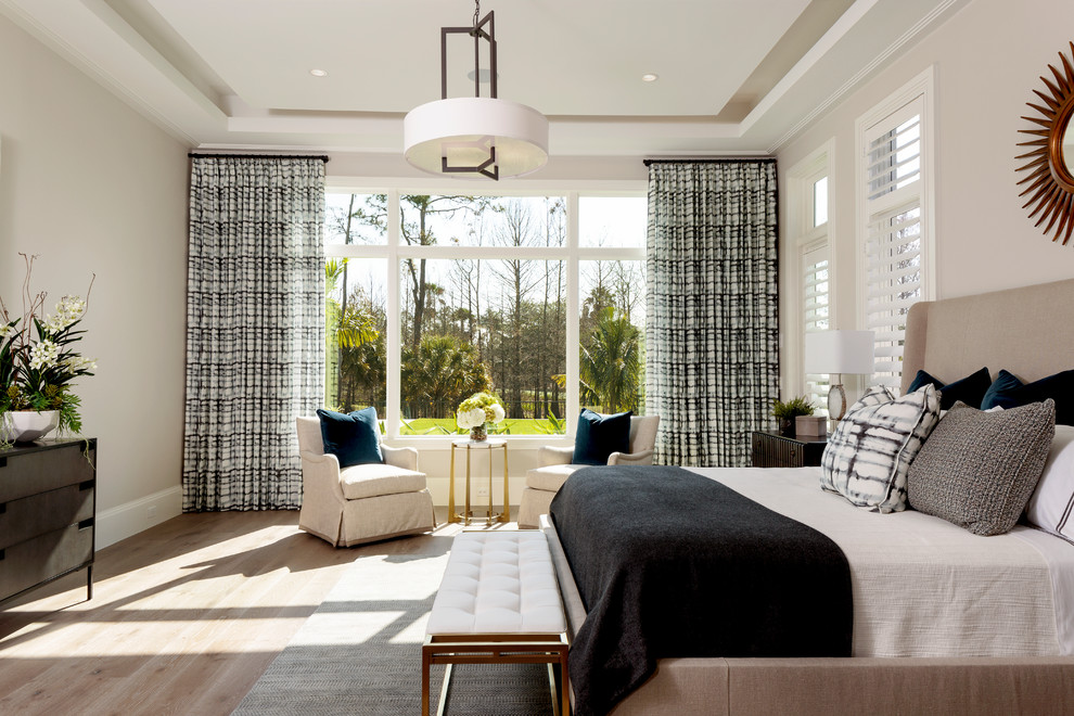Inspiration for a large transitional master light wood floor and beige floor bedroom remodel in Miami with beige walls and no fireplace