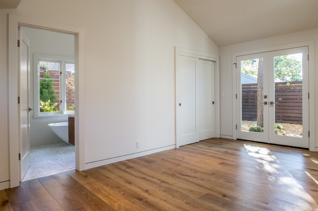 Design ideas for a medium sized modern master bedroom in San Francisco with white walls, medium hardwood flooring and no fireplace.
