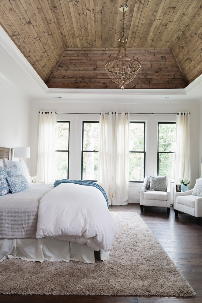 Example of a farmhouse master medium tone wood floor and brown floor bedroom design in Birmingham with white walls