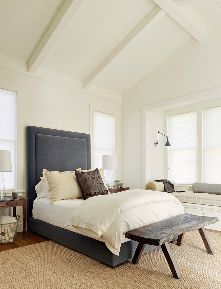 Cottage medium tone wood floor bedroom photo in San Francisco with white walls