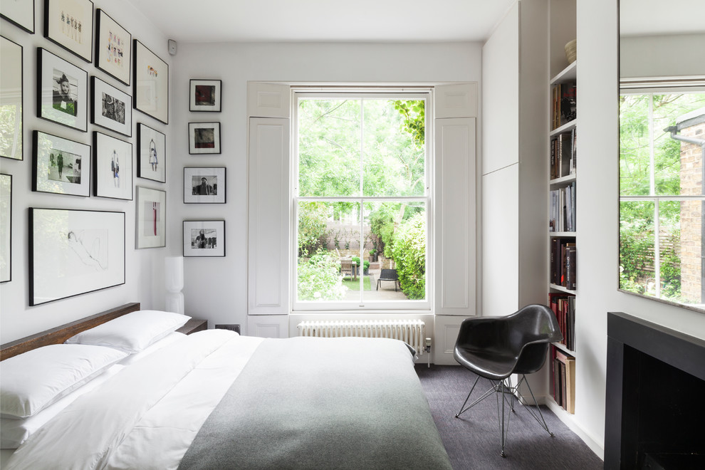 Example of a trendy guest carpeted bedroom design in London with white walls and a standard fireplace