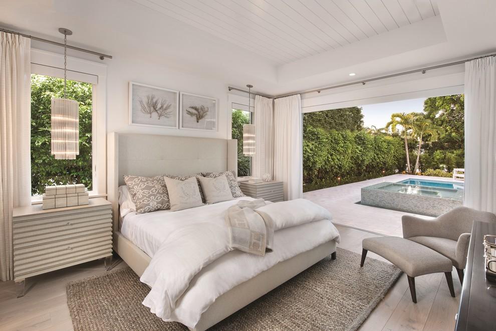 Bedroom - coastal master light wood floor bedroom idea in Miami with white walls