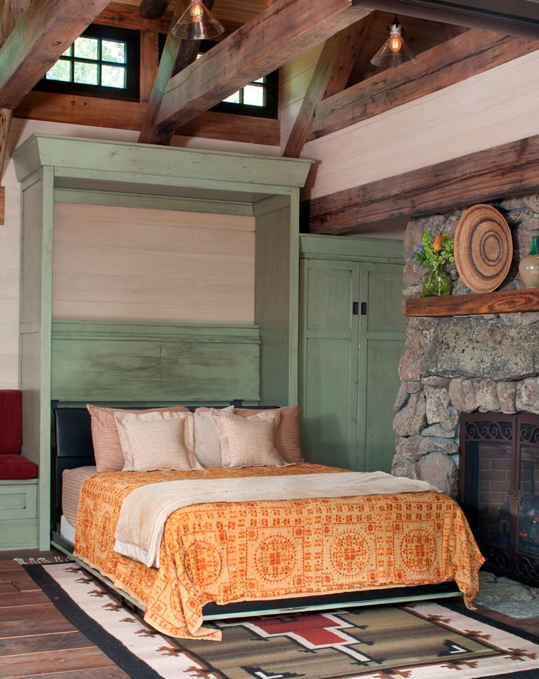 Small mountain style guest medium tone wood floor bedroom photo in Denver with a standard fireplace and a stone fireplace