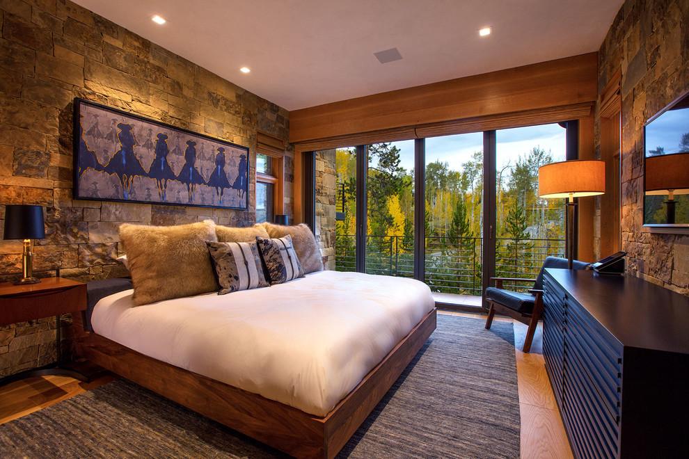 Immagine di una camera da letto rustica con pareti grigie, pavimento in legno massello medio e pavimento marrone