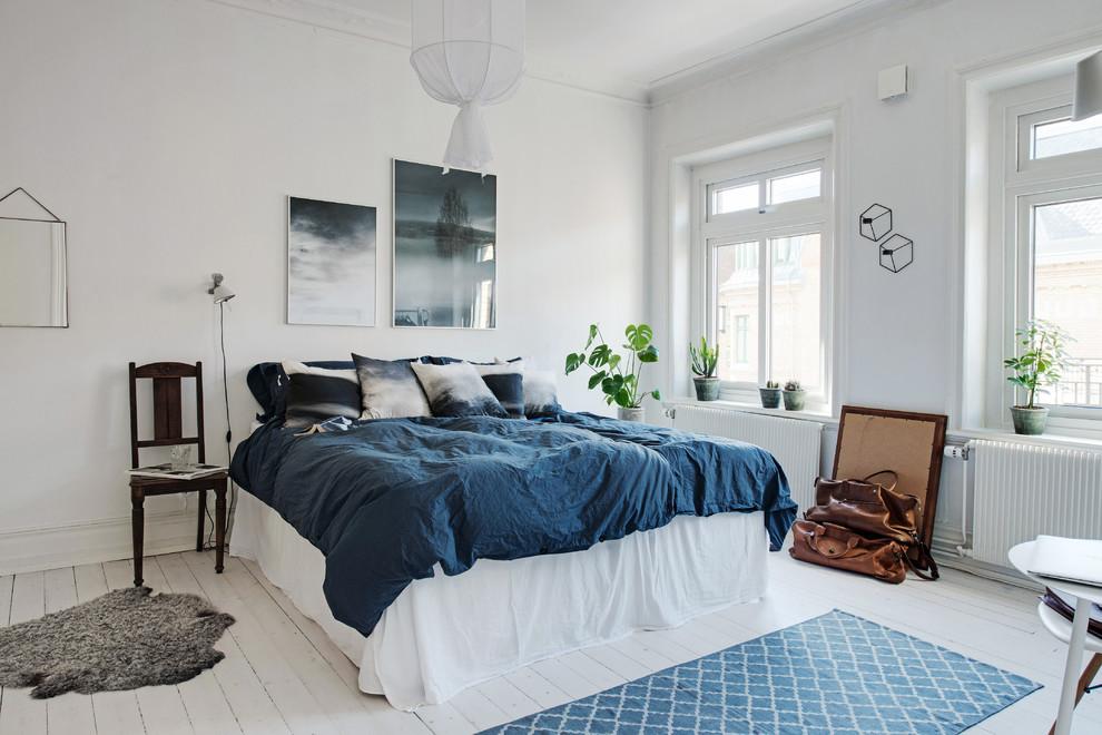 Foto di una grande camera padronale scandinava con pareti bianche, pavimento in legno verniciato e nessun camino