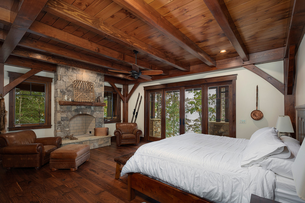 Example of a mountain style medium tone wood floor and brown floor bedroom design in Other with white walls, a standard fireplace and a stone fireplace