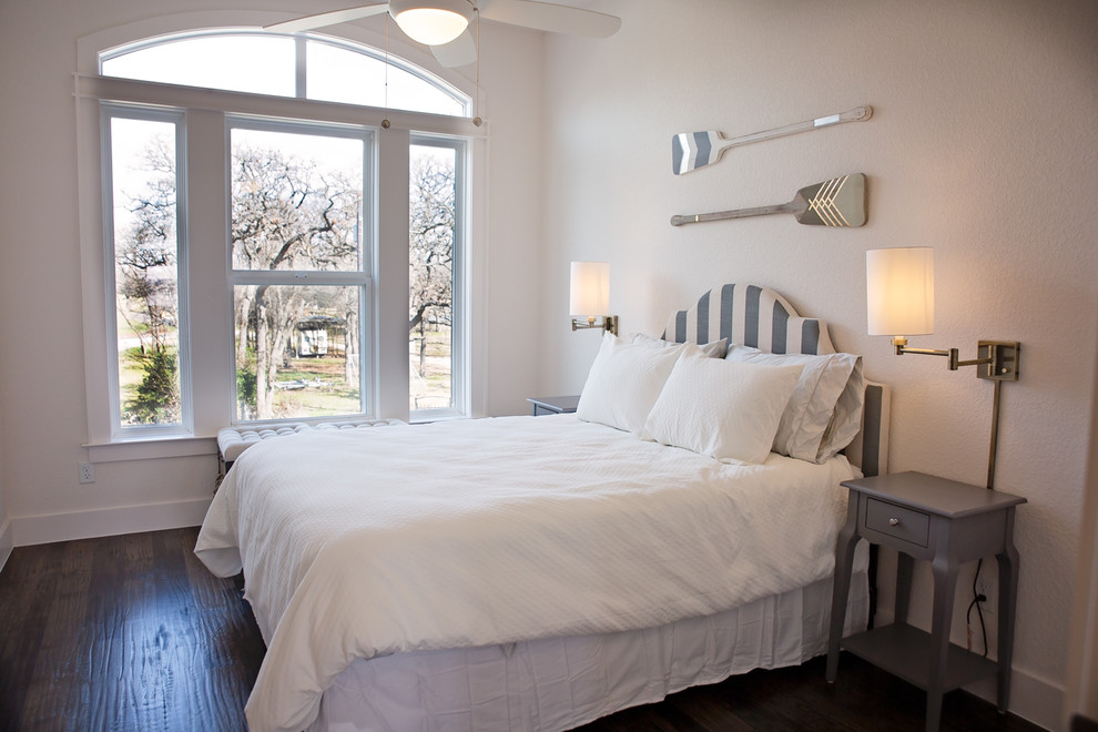Example of a large beach style guest dark wood floor and brown floor bedroom design in Dallas with white walls and no fireplace