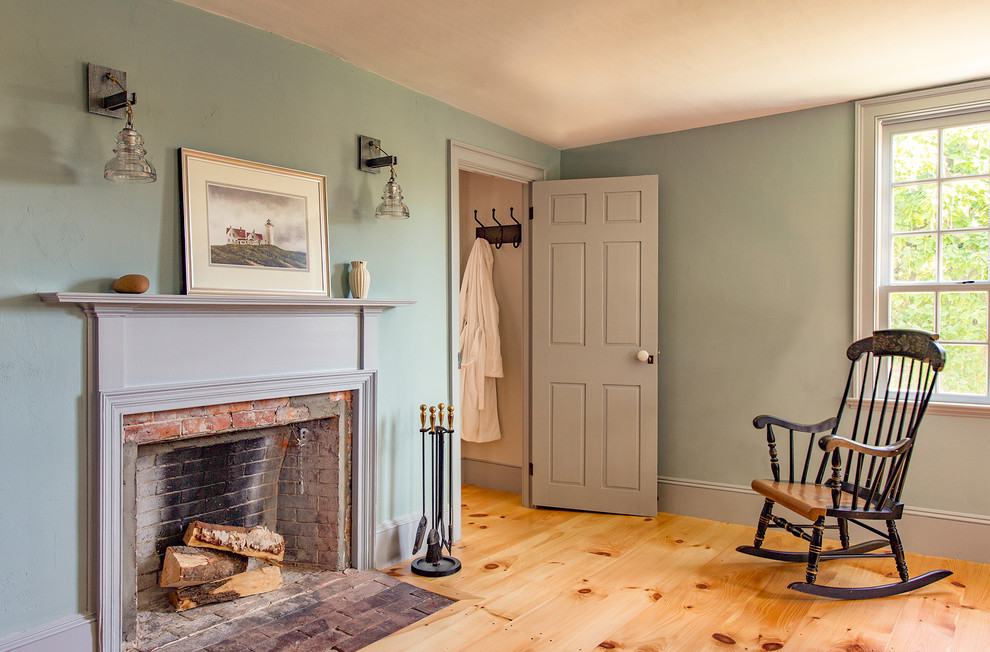Inspiration for a mid-sized farmhouse master light wood floor bedroom remodel in Boston with blue walls, a standard fireplace and a brick fireplace