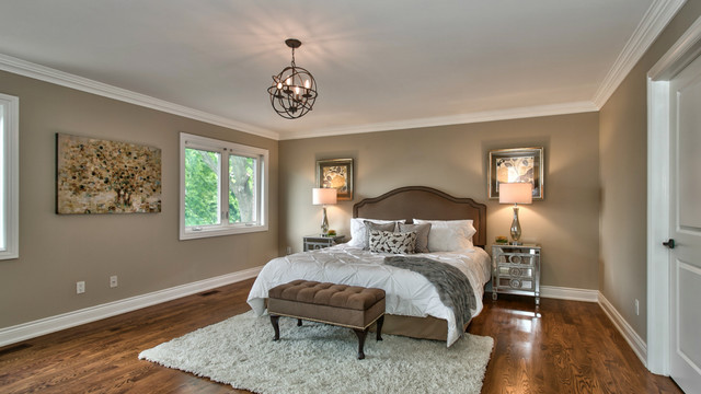 Example of a large classic master medium tone wood floor and brown floor bedroom design in Toronto with brown walls and no fireplace