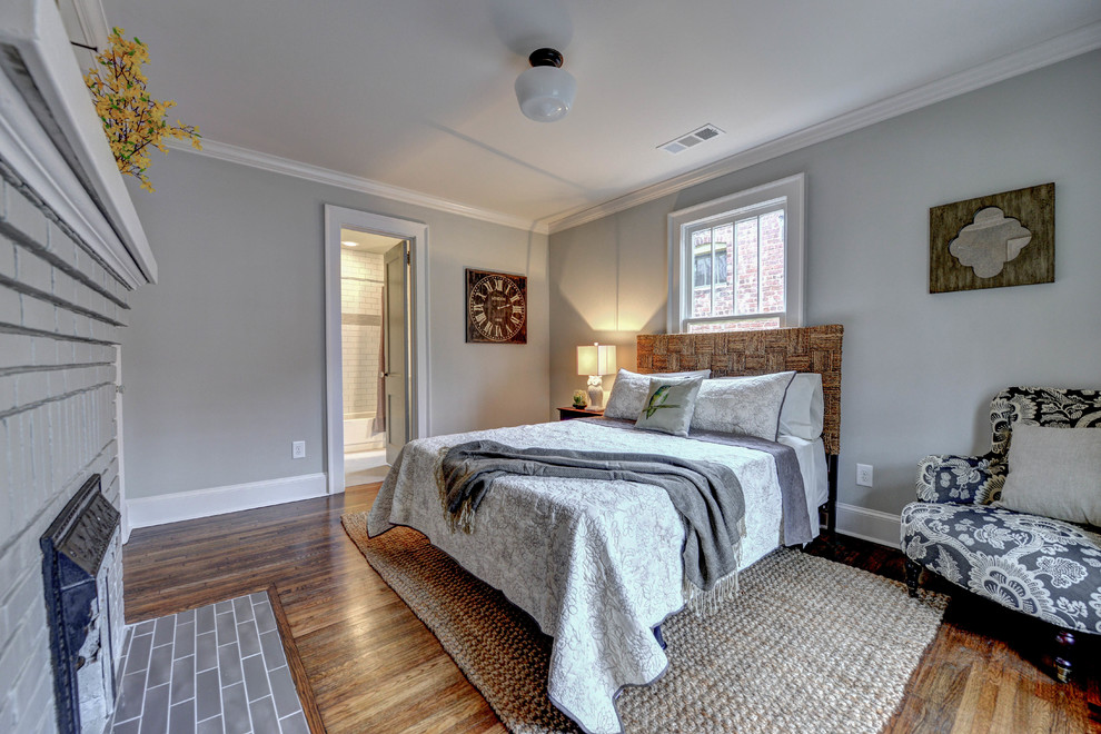 Small elegant guest medium tone wood floor bedroom photo in Atlanta with gray walls, a standard fireplace and a brick fireplace