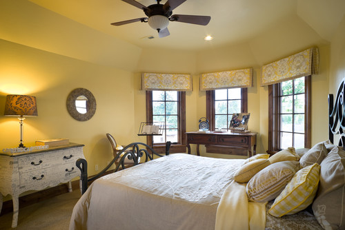 Yellow bedroom with wood trim and wrought iron bed