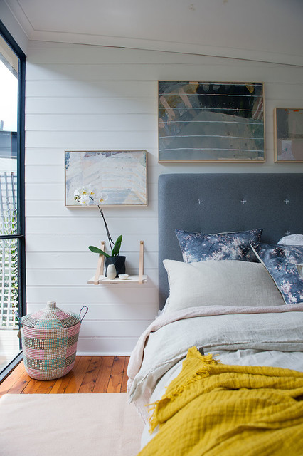This is an example of a mid-sized scandinavian bedroom in Perth with white walls and medium hardwood floors.