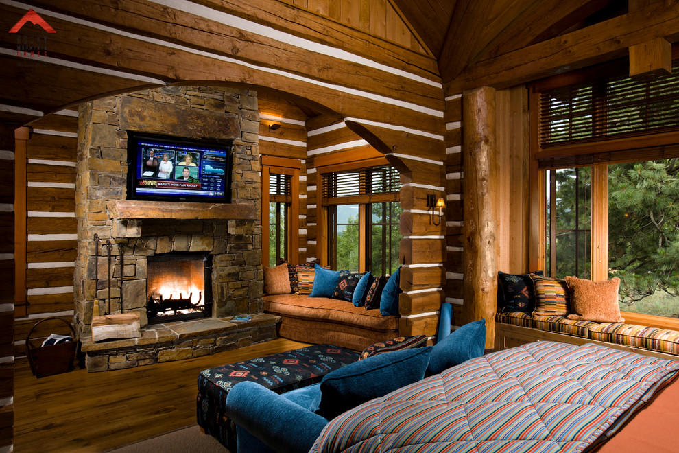 Example of a mountain style bedroom design in Other with a standard fireplace and a stone fireplace
