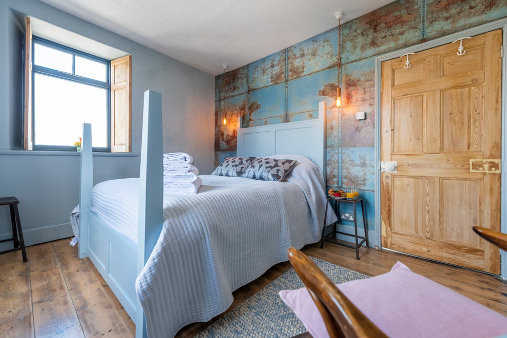 Example of a mid-sized urban medium tone wood floor and brown floor bedroom design in Cornwall with blue walls